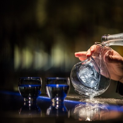 A bartender pours a mixed drink at Hakkasan Jakarta, which showcases an extensive cocktail selection.